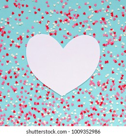 Background of colorful hearts with paper heart for text on blue background. Love and Valentine's Day concept. Copy-space background. Overhead shot