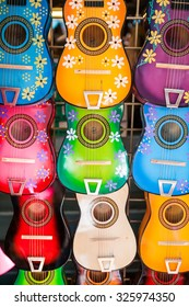 Background of colorful traditional mexican guitars on market.