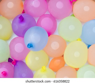 background of colorful water balloons ready for action on a hot summer day