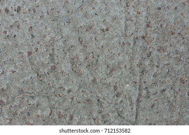 Background from concrete with impregnations from red granite gravel with an uneven surface