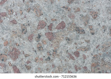 Background from concrete with large impregnations of red granite with an uneven surface