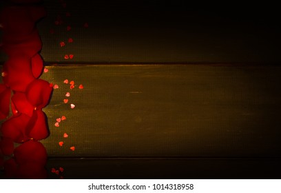Background for a congratulatory text. For St. Valentine's Day. Petals of a red rose and red cofetti on wooden boards.