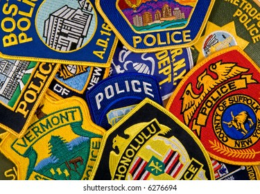 A background consisting of assorted police uniform shoulder patches.
