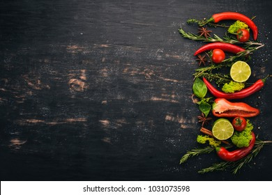 The background of cooking. A set of spices and fresh vegetables. Top view. Free space for your text. On a wooden background.