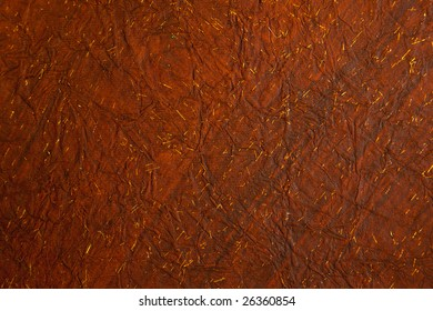Background of crushed deep reddish brown, creased rice paper with tiny flecks of gold