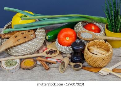 Arrière-plan pour une décoration culinaire avec spatules en bois, épices, herbes, tomates, poivre doux, courgette, panier en bois, vue frontale à 45 degrés.