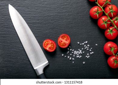 Background of cut, fresh red tomatoes on the vine with a cutting knife on black slate stone