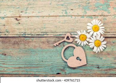 Background with daisies, lock-heart and key on old boards with shabby paint. Place for text. Top view.