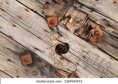 Background, damaged construction out of weathered wood plancs with rusty screws