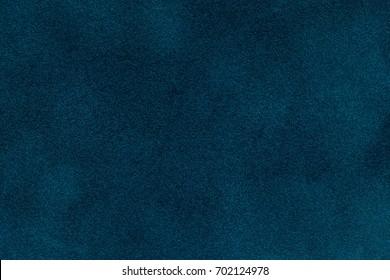 Background of dark blue suede fabric closeup. Velvet matt texture of navy blue nubuck textile.