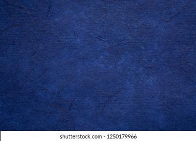background of dark blue textured handmade mulberry paper