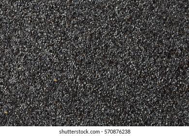 background of dark dry raw poppy seeds background.