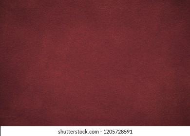 Background of dark red suede fabric closeup. Velvet matt texture of wine nubuck textile with gradient. Marron felt backdrop, vignette.