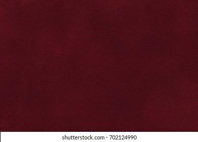 Background of dark red suede fabric closeup. Velvet matt texture of wine nubuck textile.