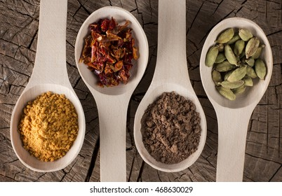 background of deep wooden spoons lying in a row on a kitchen table with spices for food: dried red pepper slices, turmeric, cinnamon, fennel seeds