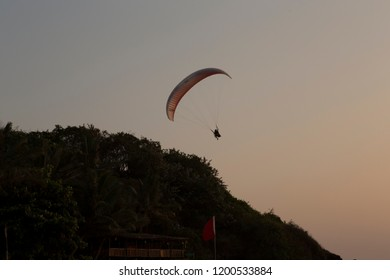 background desktop theme alone skyglider sportsman skygliding red parachute high in  sky contrast silhouette  in action full of adrenaline above palm trees on travel sport leisure holiday in Goa India