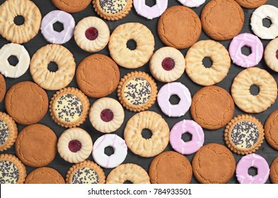 Background of different sweet biscuits on a black wooden table, top view