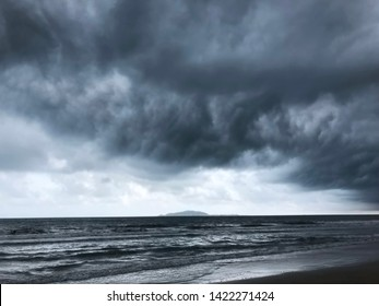 background of dramatic heavy dark clouds over the dark beach