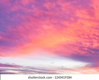 Background with dramatic storm clouds at sunset, in magenta, pink and orange colors.