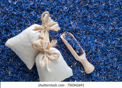 Background of dry blue cornflower, two sachet bags and wooden scoop. Top view.