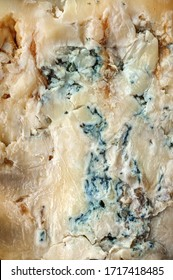 Background of English Stilton cheese texture with blue mold. A piece of Stilton blue cheese
