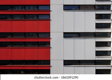 Background of exterior facade of modern building with detail of red and white aluminium panels and black dark reflected glass on horizontal windows.
