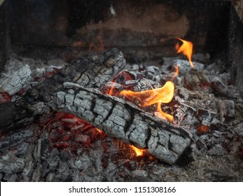 Background of fireplace with gloving embers. Close up view on smouldering fire. Embers burning with red and yellow flame. Texture of ash and glowing embers. Blurred background. Soft selective focus
