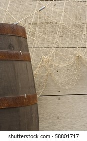 Background of fish net, weathered boards and a barrel.