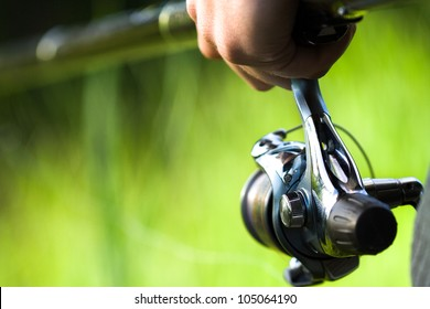 Background with a fisherman holding rod and weed in the background. Fishing reel visible. Setup for a peaceful catching of trench, crucian, bremes or other fish. Selective focus