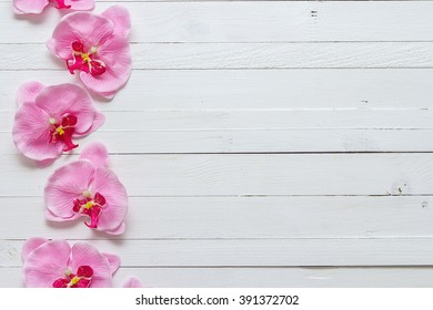 Background with flowers pink orchid on painted wooden planks. Place for text. Top view with copy space