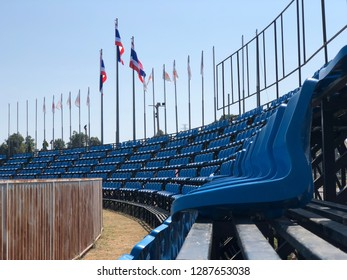 Background focus on outdoor sports grandstand chairs in the daytime.
