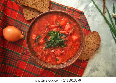 Background food on the table. Ukrainian and Russian cuisine. Red borsch on a light background. Red checkered textile. Borsch with vegetables and tomato. Beets, onions, bread, tomato, cabbage, parsley.