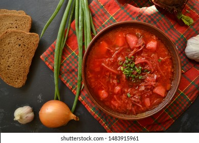 Background food on the table. Ukrainian and Russian cuisine. Red borsch on a black background. Red checkered textile. Borsch with vegetables and tomato. Beets, onions, bread, tomato, cabbage, garlic.