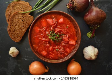 Background food on the table. Ukrainian and Russian cuisine. Red borsch on a black background. Borsch with vegetables and tomato. Beets, onions, bread, tomato, cabbage, garlic.
