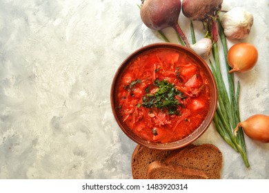 Background food on the table. Ukrainian and Russian cuisine. Red borsch on a light gray background. Borsch with vegetables and tomato. Beets, onions, bread, tomato, cabbage, garlic.