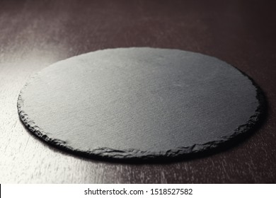 Background for food placement. Slate Board on a wooden table. 45 degree angle view.