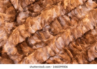 Background in the form of natural pieces of mink fur brown color located diagonally from left to right