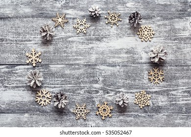 Background with a frame of decorative wooden snowflakes and white painted pine cones on gray wooden table. Space for text. Top view.