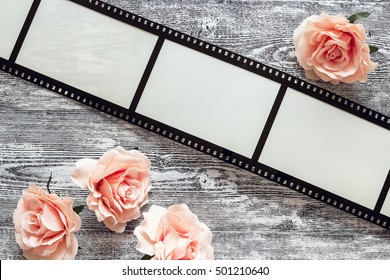 Background with a frame in the form of a film, and pink roses on gray wooden table. Space for text or image.