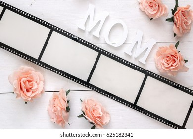 Background with a frame in the form of a film, pink roses and mothers day message on white wooden table. Space for text or image.