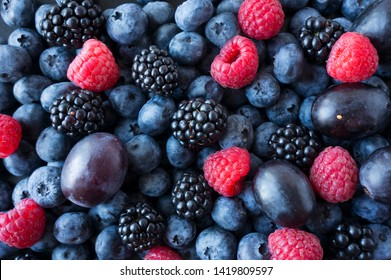 Background of fresh fruits and berries. Ripe blackberries, blueberries, plums, raspberries. Mix berries and fruits. Top view. Background berries and fruits. Black-blue and red food. - Shutterstock ID 1419809597