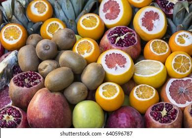 Background of fresh fruits of pomegranate oranges kiwi, pineapple
