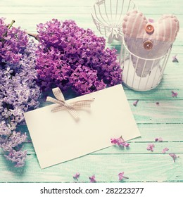 Background  with fresh lilac flowers,  textile decorative heart  and empty tag on turquoise painted wooden planks. Selective focus. Place for text. Square image.