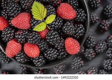 Background from fresh organic blackberries and raspberries, close up. Lot of ripe juicy wild fruit raw berries in a black plate. Top view blackberry and raspberry
