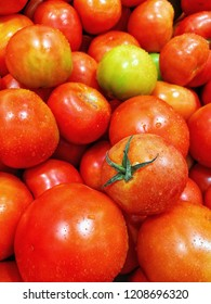 background of fresh organic red orange green juicy ripe tomato for sale at farmers market grocery store, best vegetable for vitamins and cooking ingredient in asian thai tomyam dishes