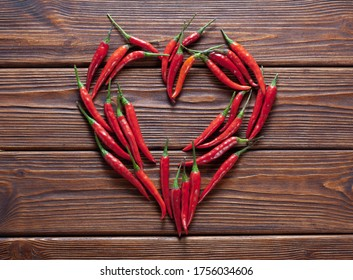 background of fresh red chili pepper arranged into heart shape. Top view