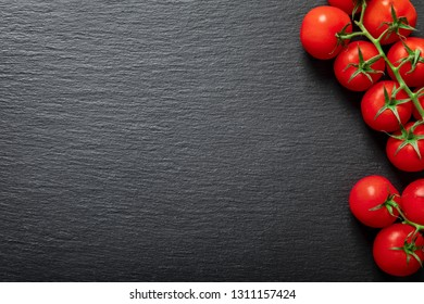 Background of fresh red tomatoes on the vine on black slate stone with copy space