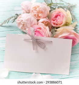 Background with fresh roses flowers and empty tag for your text on turquoise painted wooden background. Selective focus in on tag. Square image.