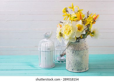 Background with fresh  spring yellow daffodils flowers and candle  on turquoise  painted wooden planks against white wall. Selective focus. Place for text.