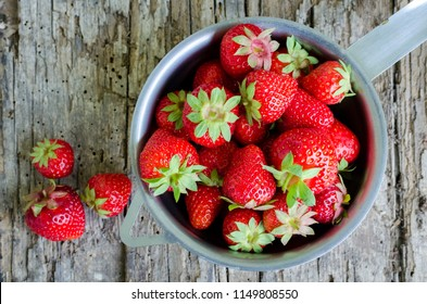 Background from freshly harvested strawberries. Metal colander filled with succulent juicy fresh ripe red strawberries on an old wooden textured table top. Directly above. Top view.